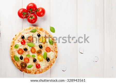 Italian pizza with cheese, tomatoes, olives and basil on wooden table. Top view with copy space - stock photo