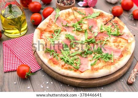 Italian pizza with ham arugula and cheese - stock photo