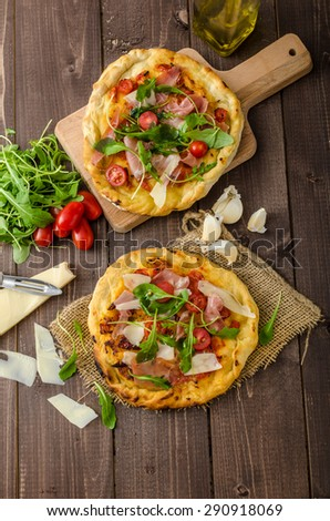 Italian pizza with parmesan cheese, prosciutto and arugula, home made, small cherry tomatoes, delicious and simple - stock photo