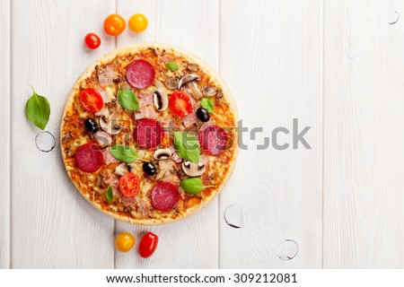 Italian pizza with pepperoni, tomatoes, olives and basil on wooden table. Top view with copy space - stock photo