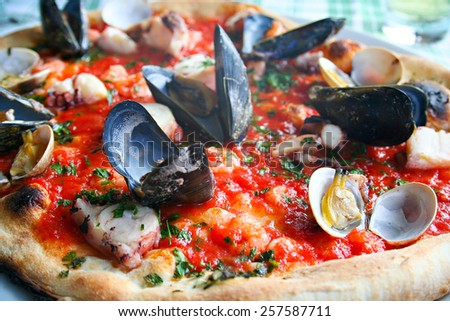 Italian pizza with seafood - octopus, calamary, mussels and clams - stock photo