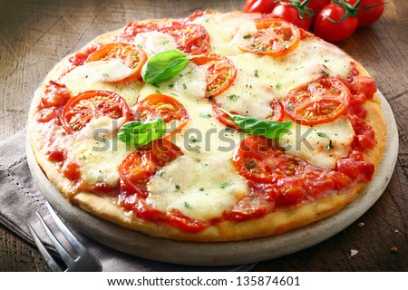 Italian pizza with tomato topped with melted golden cheese, herbs and basil served on a round wooden board on an old wood table - stock photo