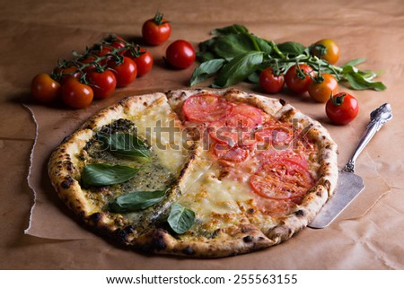 Italian pizza with tricolor Italian flag cut slices and cherry tomatoes and fresh basil at confectionery paper - stock photo