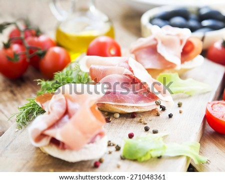 Italian Prosciutto Appetizer with Spices on a Wooden Cutting Board Ready to be Served - stock photo