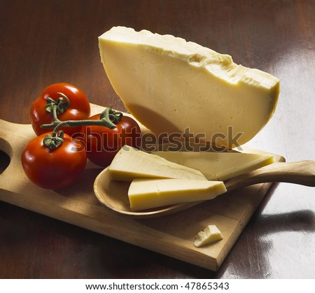 Italian provolone and tomatoes on wooden board - stock photo