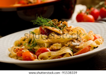 Italian regional dish made of pasta with sardines on wooden table - stock photo