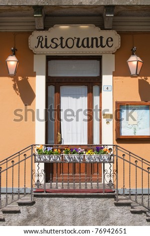 Italian restaurant door with stairs,flowers and blank menu on display - stock photo