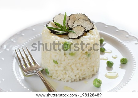 Italian risotto with black truffle and green peas on white plate - stock photo