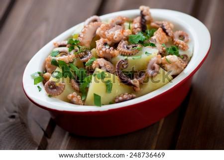 Italian salad with chopped octopus, potato and parsley - stock photo