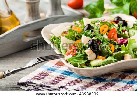 Italian salad with fresh vegetables with black olives and Parmesan cheese. Vintage scenery.