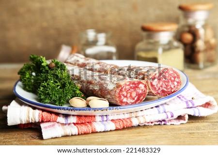 Italian salami on plate, on wooden background - stock photo