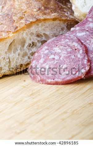Italian salami sausage sliced with brick oven delicious fresh baked bread for sandwich - stock photo