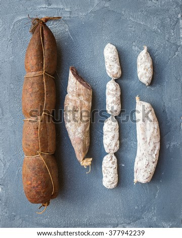 Italian salami sausages of different kinds over a rough grey-blue concrete background, top view - stock photo