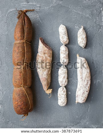Italian salami sausages of different kinds over a rough grey concrete background, top view - stock photo