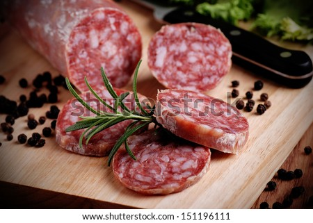 Italian salami sliced �¢??�¢??on wooden table - stock photo