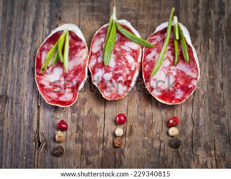 Italian salami sliced on wooden table - stock photo