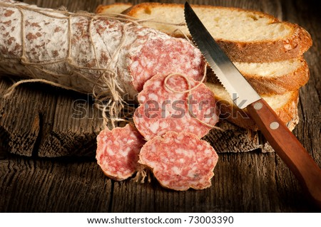 italian salami with slice bread and knife - stock photo