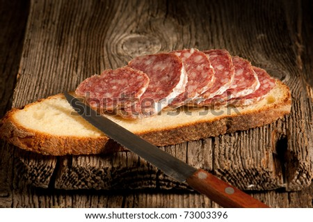 italian salami with slice bread and knife - stock photo