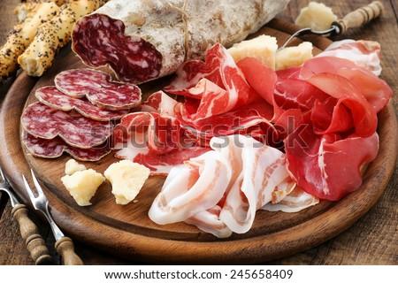 Italian salumi meat platter - prosciutto ham, bresaola, pancetta, salami and parmesan - stock photo