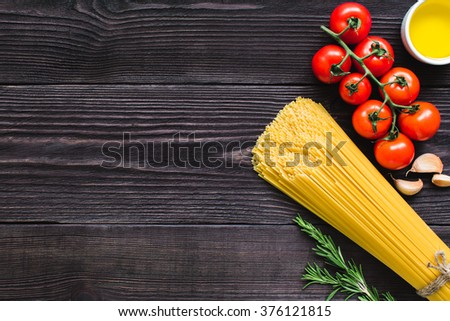 Italian spaghetti on a wooden table with bunch tomatoes, rosemary, garlic and cup of oil. Top view. - stock photo