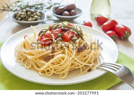 italian spaghetti pasta with cherry tomatoes, olives, capers and rosemary, mediterranean food, vegan recipe - stock photo