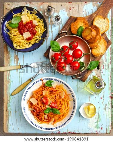 Italian spaghetti pasta with tomato, basil, parmesan, olives and fork - stock photo