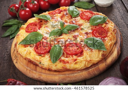 Italian spaghetti pizza with cheese and cherry tomato
