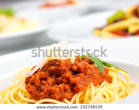 Italian spaghetti topped with bolognaise, or bolognese, sauce with tomatoes, meat and cheese on a plain white plate - stock photo