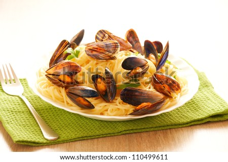 Italian spaghetti with mussels cooked in white wine sauce, served with parsley - stock photo