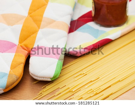 Italian spaghetti with tomato sauce and kitchen glove on the table. - stock photo