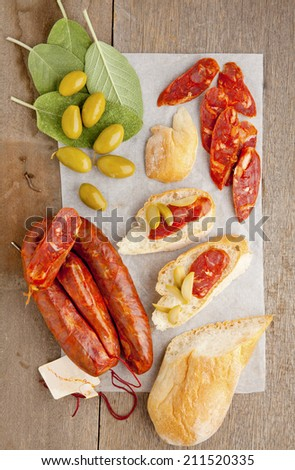 italian spicy sausage, bruschetta, sage leaves, green olives, fresh bread, on wooden table on white - stock photo