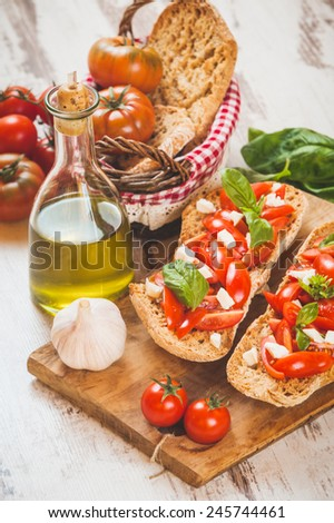 Italian starter, bruschetta with Sicilian red fresh tomato and mozerella cheese on a wooden background - stock photo