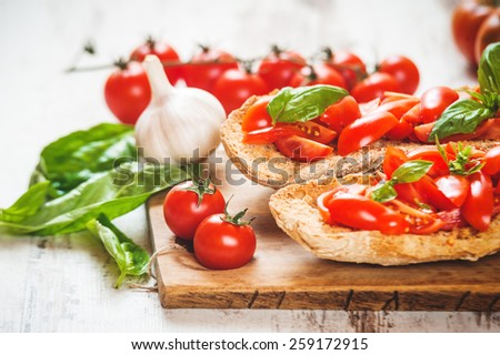 Italian starter, bruschetta with Sicilian red fresh tomato on a wooden background - stock photo