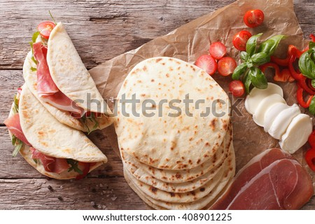 Italian street food: piadina with ham, cheese and vegetables close-up on the table. horizontal view from above