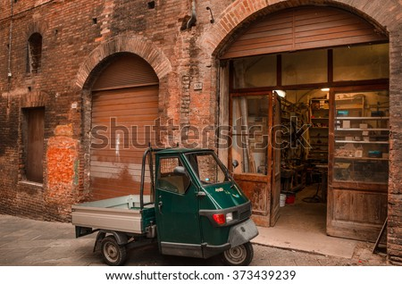 Italian street - Retro urban scene. An dark green Ape car parked in front of a repair shop in an old street of Siena, in the Italian Tuscany. Photo taken on: October 18th, 2013 - stock photo