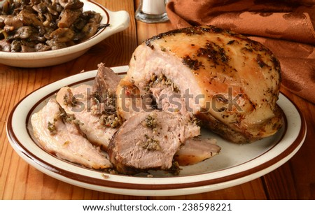 Italian style porchetta pork roast stuffed with red and green bell peppers, garlic, onion, rosemary and more - stock photo