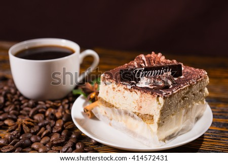 Italian stylish dessert with a piece of Tiramisu cake on a white saucer and a cup of black coffee surrounded by roasted beans scattered on a wooden table - stock photo