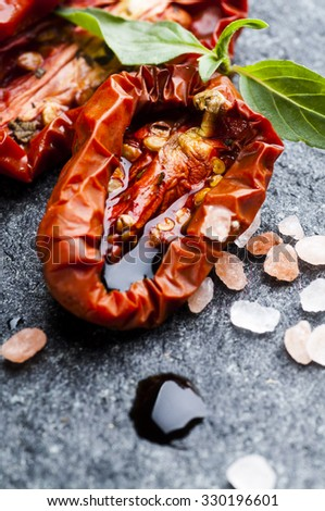 Italian sun dried tomatoes with balsamic vinegar, basil leaves and Himalayan  pink salt on stone background  - stock photo
