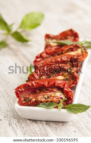 Italian sun dried tomatoes with spices and basil leaves in plate on wooden table