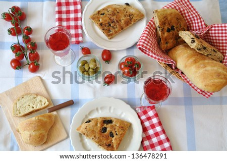 Italian Table setting with fresh bread, red wine and vegetables - stock photo
