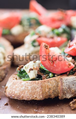 Italian tomato and vegetable bruschetta with chopped spinach, herbs and cheese on grilled or toasted crusty ciabatta bread - stock photo