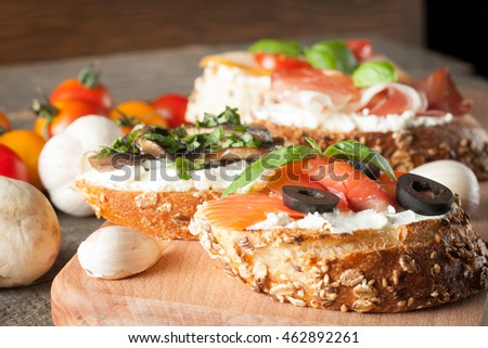 Italian tomato, mushrooms, prosciutto, salmon and cheese bruschetta. Tapas, antipasti with chopped vegetables, herbs and oil on grilled ciabatta and baguette bread.