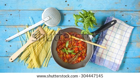 italian tomato sauce with spaghetti and food ingredients, kitchen utensils - stock photo