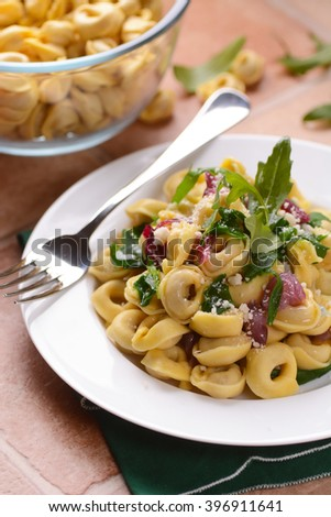Italian tortellini with rocket and red onion