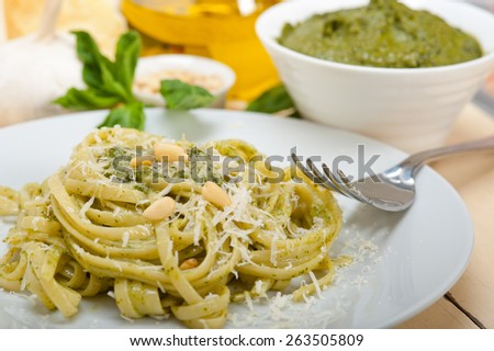 Italian traditional basil pesto pasta ingredients parmesan cheese pine nuts extra virgin olive oil garlic on a rustic table  - stock photo