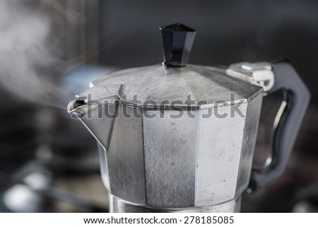 Italian traditional coffeemaker with hot coffee flowing out from the spout - stock photo