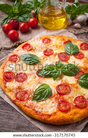 Italian traditional pizza margherita. Homemade baked delicious meal with basil tomatoes and mozzarella on vintage wooden table background. Rustic style and natural light.