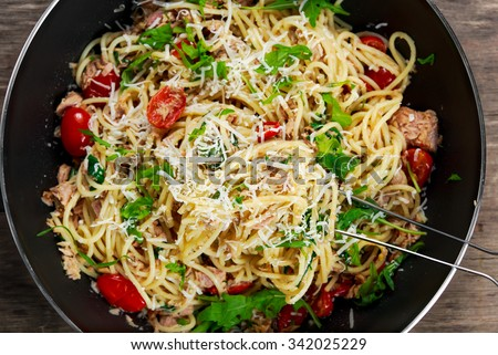 Italian Tuna Pasta spaghetti in wok, with tomato, chili, Parmesan cheese and wild rocket  lives. on old wooden table - stock photo