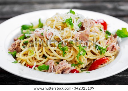 Italian Tuna Pasta  spaghetti with tomato, chili, Parmesan cheese and wild rocket  lives. on old wooden table - stock photo