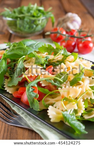 italian type pasta called farfalle butterflies, rucola and little tomatoes
